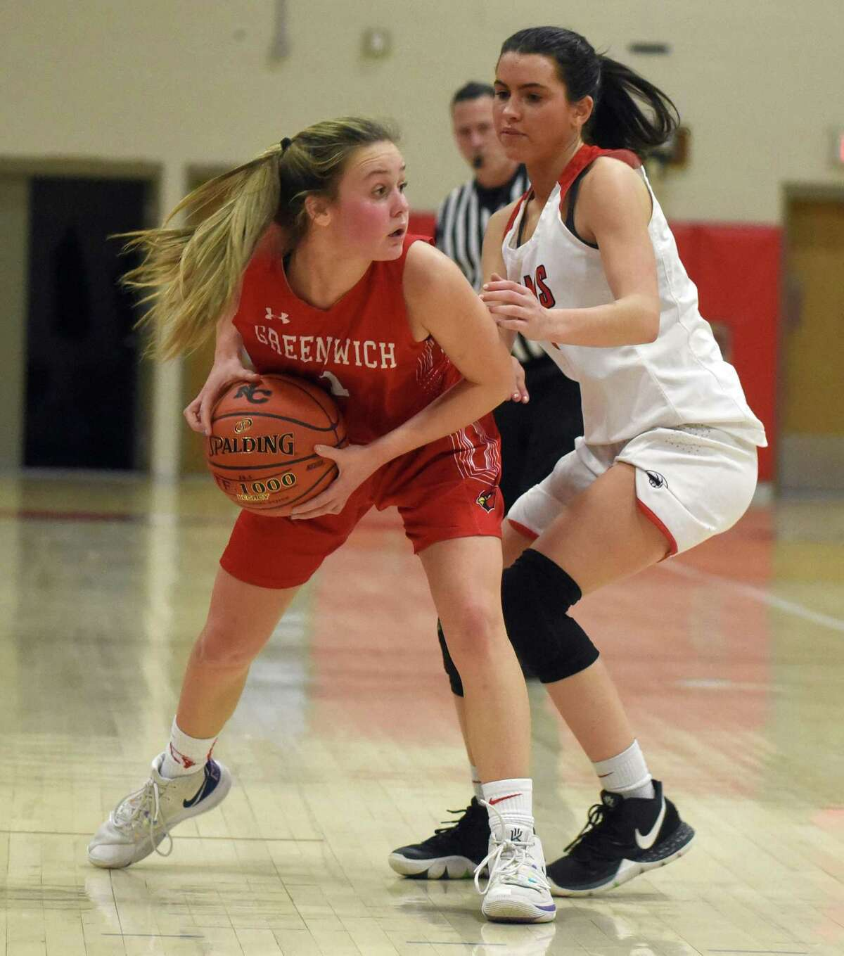 Greenwich's Ava Sollenne (1) looks to pass while under pressure from New Canaan's Riana Afshar during a girls basketball game at New Canaan High School on Tuesday, Jan. 7, 2020.