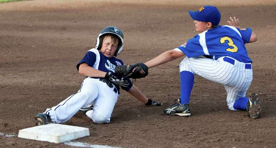 Newton, Connecticut's third baseman #3, Colby Olson tags Jupiter runner #13, Brett Steel out at third after Olson hit a double and attempted to take three bases on his hit. The Newton CT Thunder played Florida Jupiter Sunday night, August 15, 2010 during the 2010 Cal Ripken Baseball 10U World Series for 10 year-olds at the Ocala Rotary Sportsplex in Ocala, Fla. Jupiter lead 5-0 at the bottom of the 3rd inning  The tournament began August 13th and runs through August 20th. There will be 12 teams from throughout the country competing for the championship. (Doug Engle/Star-Banner)2010 Photo: Doug Engle, Star-Banner / Star-Banner