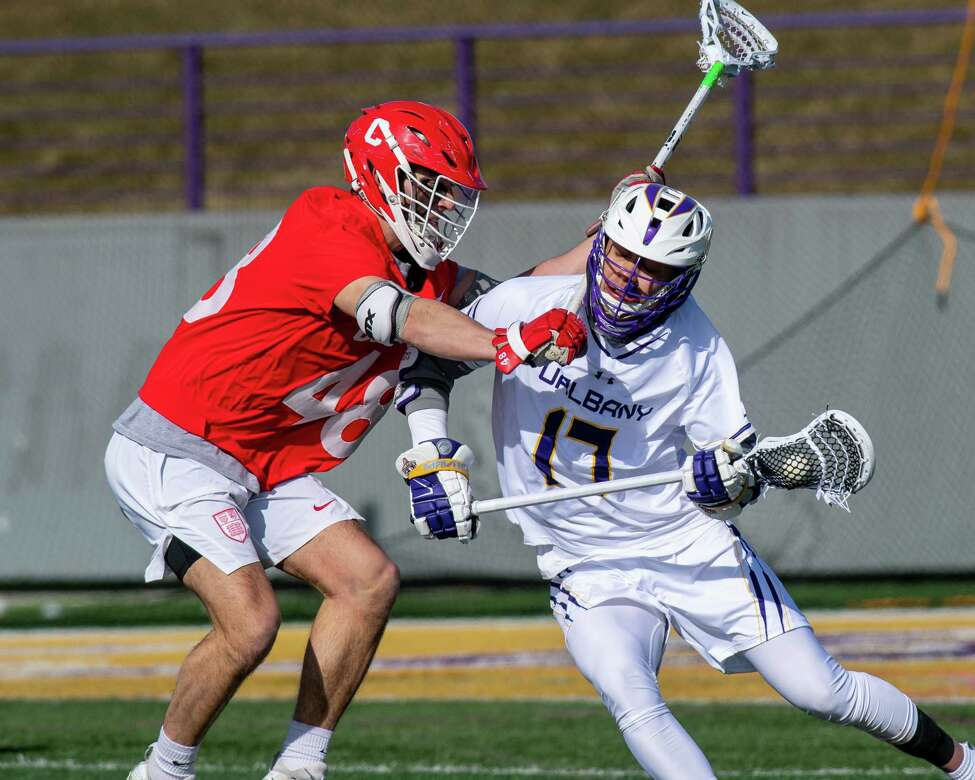 UAlbany senior Jakob Patterson takes a stick check to the neck by Cornell University senior Brandon Salvatore during the season opener at UAlbany on Saturday, Feb. 15, 2020 (Jim Franco/Special to the Times Union.)