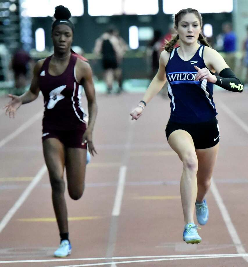 Wilton's Shelby Dejana, right, wins the 55-meter dash during the Class L indoor track championship on Saturday. Photo: Peter Hvizdak / Hearst Connecticut Media / New Haven Register
