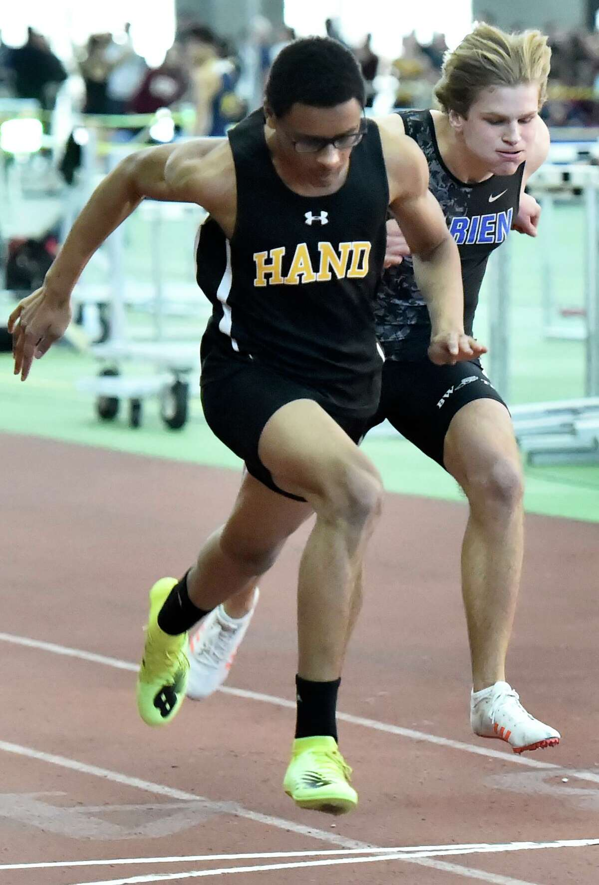 Hand's Joshua Stewart, left, edges out Darien's Nicholas Balenzano during the 55-meter dash preliminaries of the Class L track championship on Saturday.