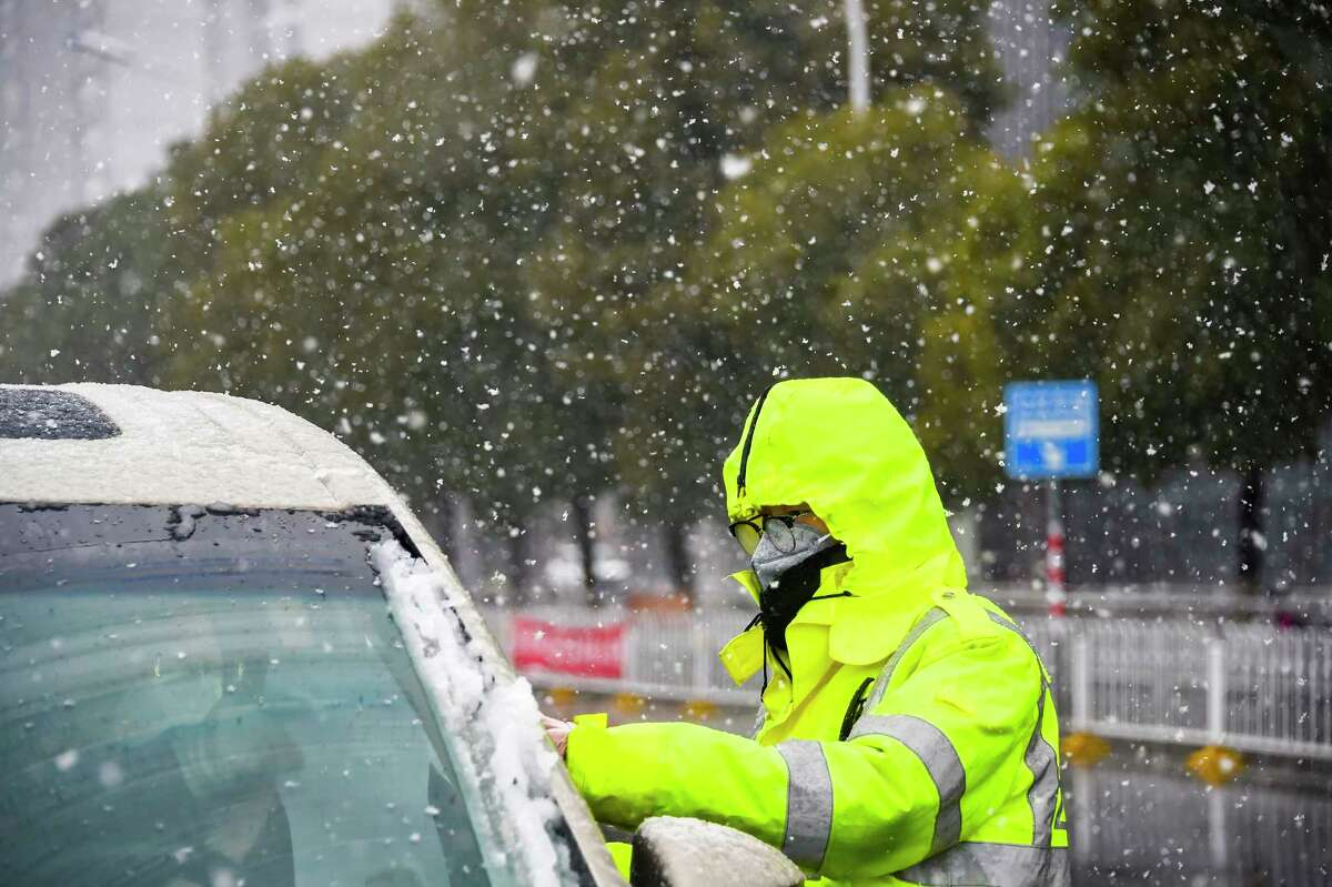 In this photo released by China's Xinhua News Agency, a traffic policeman wearing a face mask checks a car during a snowfall in Xiaogan in central China's Hubei Province, Saturday, Feb. 15, 2020. The virus is thought to have infected more than 67,000 people globally and has killed at least 1,526 people, the vast majority in China, as the Chinese government announced new anti-disease measures while businesses reopen following sweeping controls that have idled much of the economy. (Hu Huhu/Xinhua via AP)