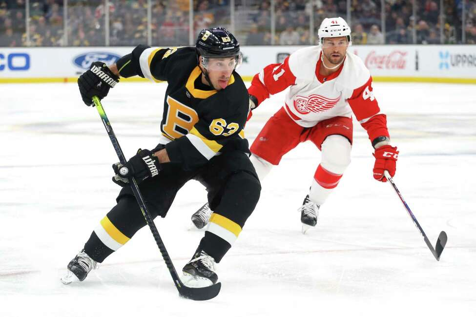 BOSTON, MASSACHUSETTS - FEBRUARY 15: Brad Marchand #63 of the Boston Bruins skates past Luke Glendening #41 of the Detroit Red Wings during the first period at TD Garden on February 15, 2020 in Boston, Massachusetts. (Photo by Maddie Meyer/Getty Images)