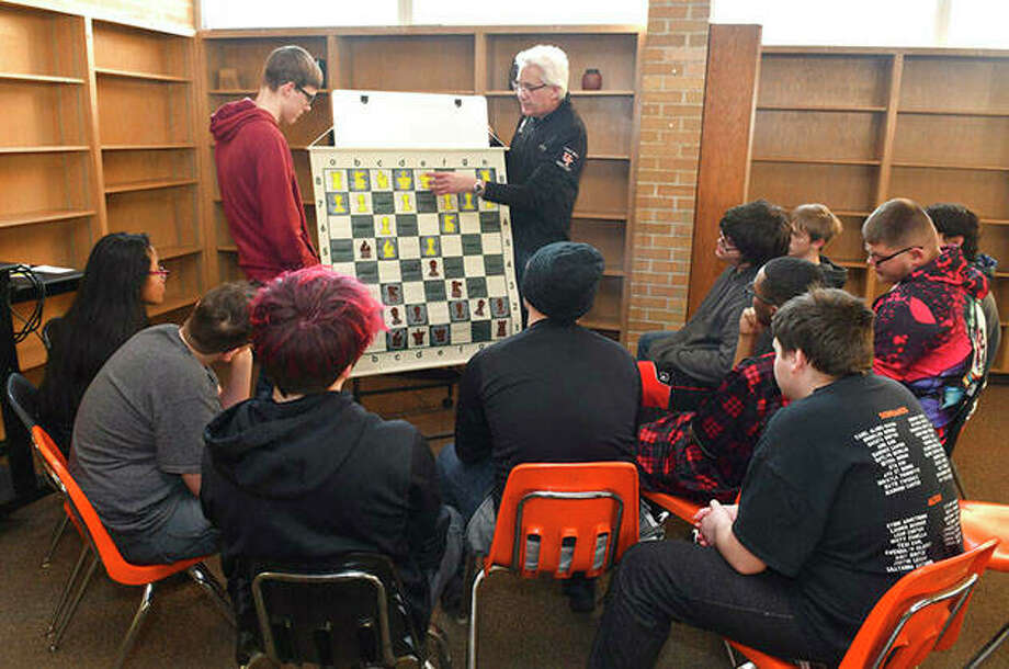 United Township student Seth Bealer and Thomas Ebalo stand with a large chess practice game board as Ebalo talks about some of the basic chess moves to students during practice. Photo: Gary Krambeck | Quad City Times (AP)