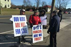 Parents protest a bill that would repeal religious exemptions for vaccinations among children in school at Thyme & Season in Hamden, Conn. on Feb. 15, 2020. The store is owned by Rep. Josh Elliott (D-Hamden), a proponent of the legislation. The man speaking with them is a passerby.