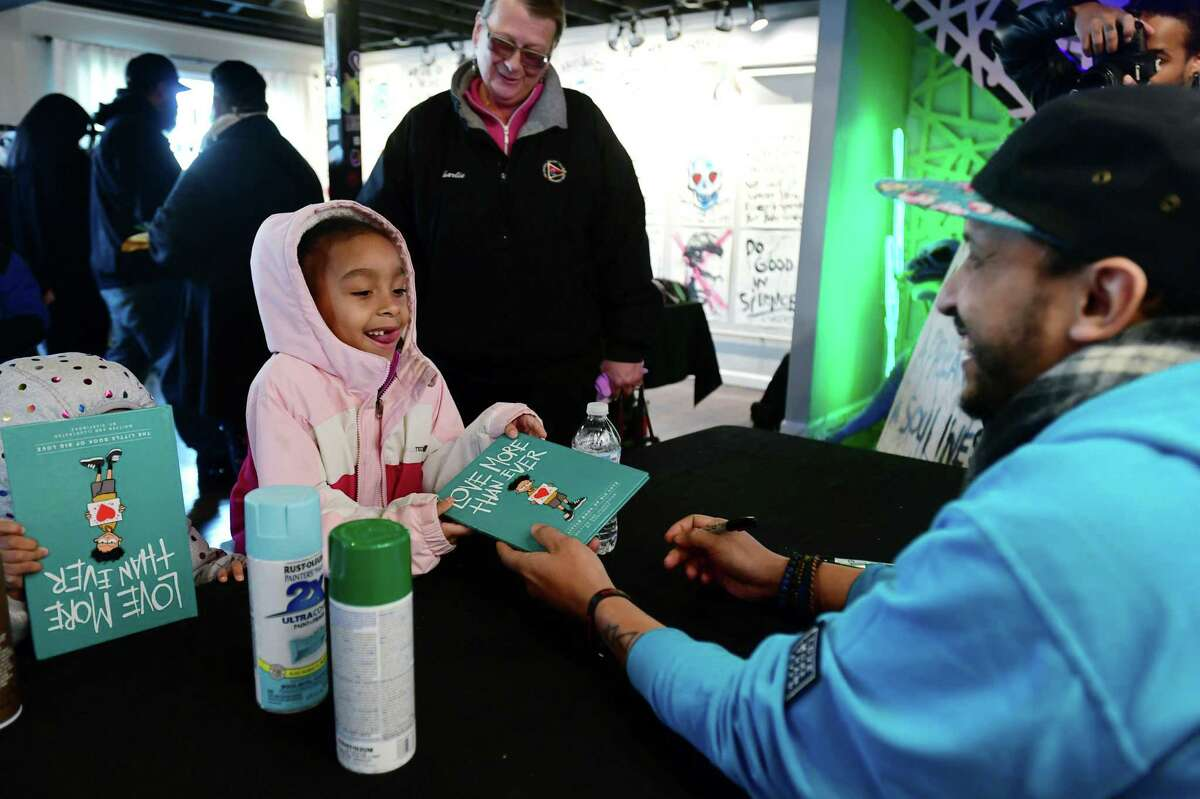Dawn Stampoulidis, Melody Harris, 2, and Mariah Simmons, 6, get their book signed as Norwalk artist 5iveFingaz holds a book signing event for his new book, Love More Than Ever, Saturday, February 15, 2020, at the Mad Lab on Leonard St. in Norwalk, Conn.