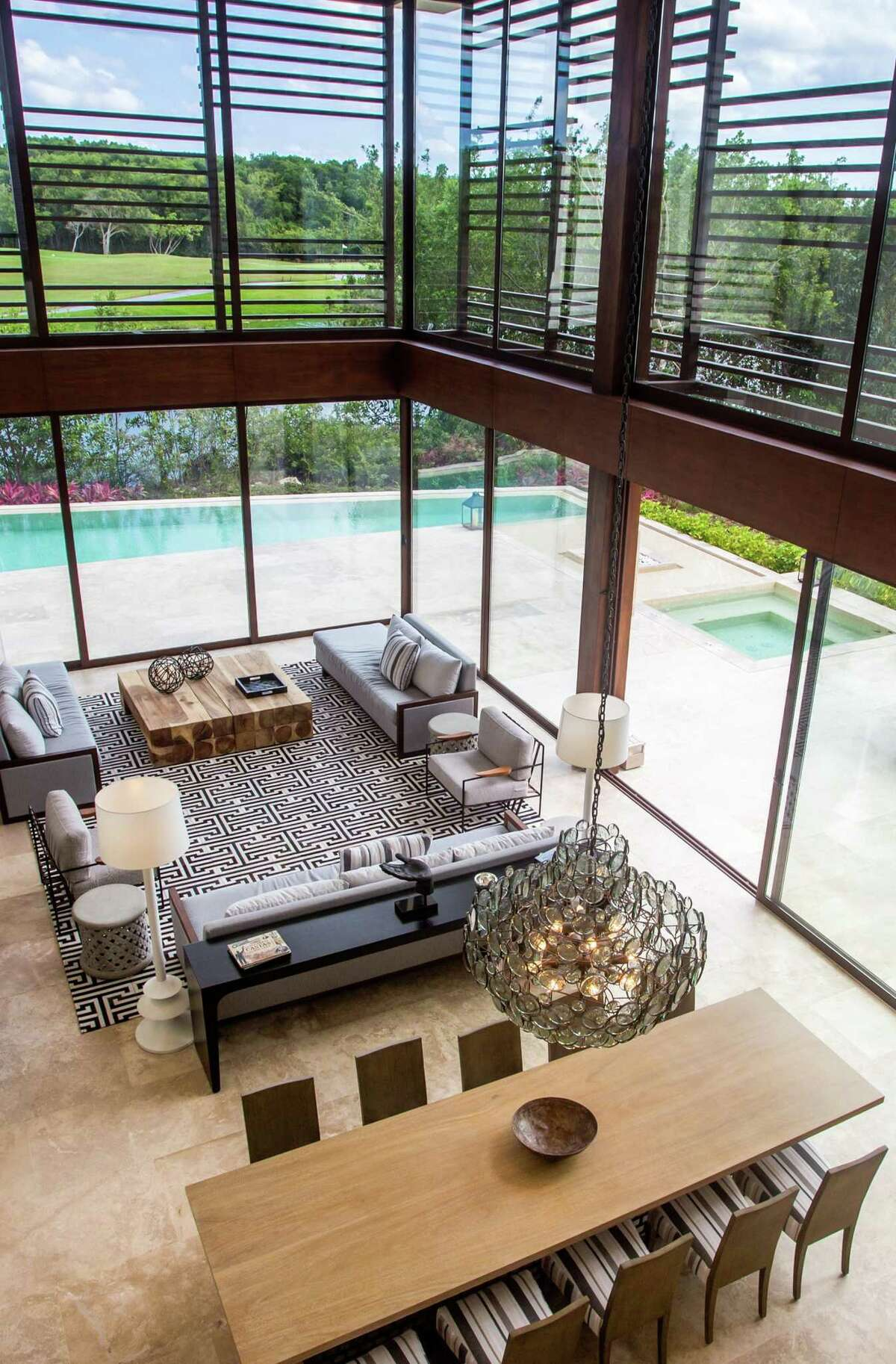 Floor-to-ceiling windows look out at the heated pool and hot tub at 832 Villa Paraíso in Cancún, Mexico.