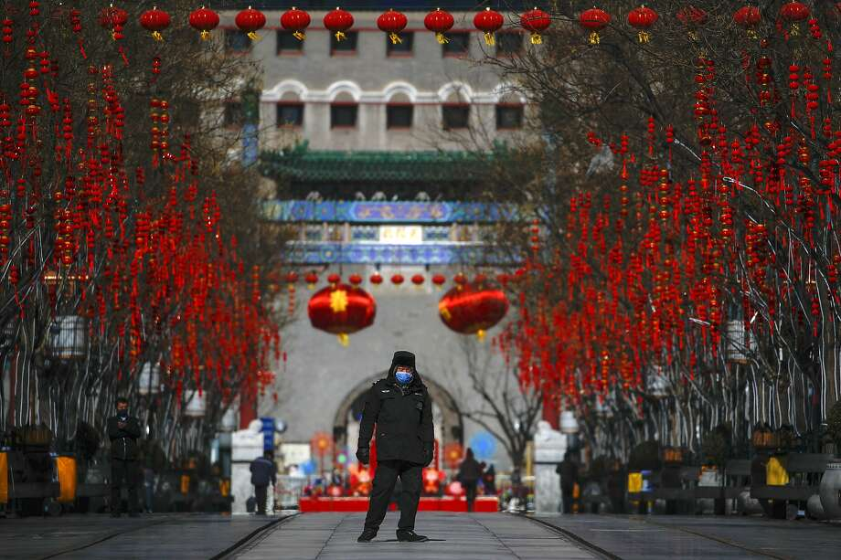 A security guard patrols a nearly empty Qianmen Street, normally a popular tourist attraction in Beijing. Photo: Andy Wong / Associated Press
