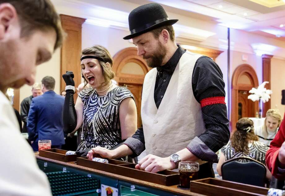 Amanda Welch (left) and Peter Buist (right) play craps during Disability Network of Mid-Michigan's annual fundraiser, Feathers and Fedoras, Saturday, Feb. 15, 2020 at the Great Hall Banquet and Convention Center. (Cody Scanlan/for the Daily News) Photo: (Cody Scanlan/for The Daily News)