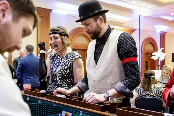 Amanda Welch (left) and Peter Buist (right) play craps during Disability Network of Mid-Michigan's annual fundraiser, Feathers and Fedoras, Saturday,Feb. 15, 2020 at the Great Hall Banquet and Convention Center. (CodyScanlan/for the Daily News)