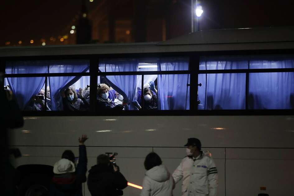 Buses carrying passengers from the quarantined Diamond Princess cruise ship leave a port in Yokohama, near Tokyo, Monday, Feb. 17, 2020. A group of Americans are cutting short a 14-day quarantine on the Diamond Princess cruise ship in the port of Yokohama, near Tokyo, to be whisked back to America. But they will have to spend another quarantine period at a U.S. military facility to make sure they don't have the new virus that's been sweeping across Asia. (AP Photo/Jae C. Hong)
