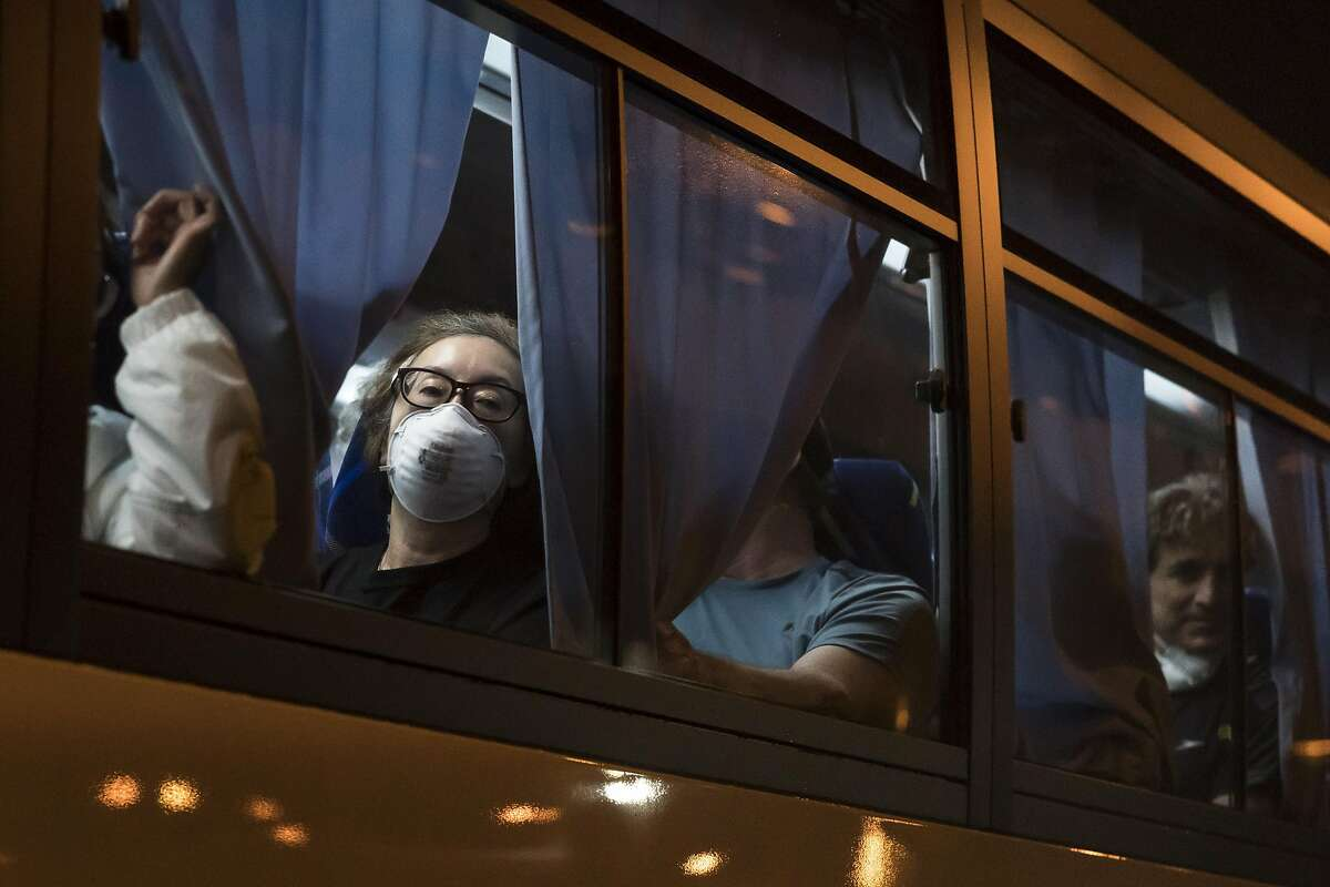 American citizens look out from a bus as they arrive at Haneda airport on February 17, 2020 in Tokyo, Japan. The United States has become the first country to offer to repatriate citizens on the Diamond Princess cruise ship while it remains quarantined in Yokohama Port as at least 355 passengers and crew onboard have tested positive for the coronavirus (COVID-19). Including cases onboard the ship, 408 people in Japan have now been diagnosed with COVID-19 making it the worst affected country outside of China.