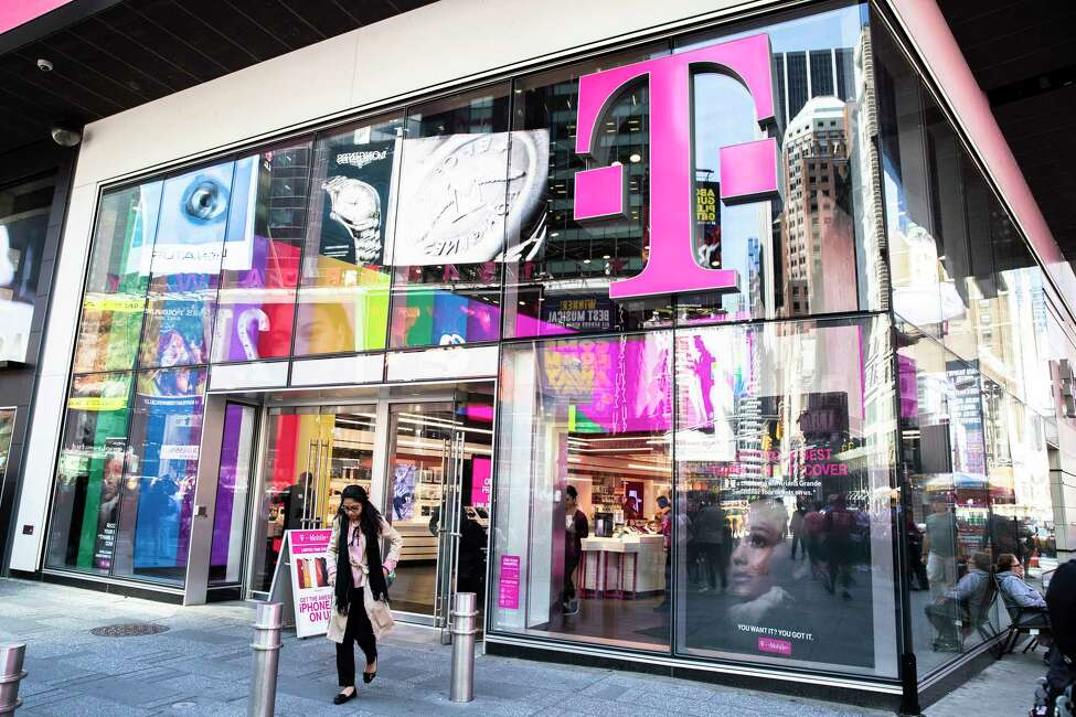 FILE -- Pedestrians outside a T-Mobile store in New York on June 11, 2019. A federal judge on Feb. 11, ruled in favor of T-Mobile's takeover of Sprint in a deal that would further concentrate corporate ownership of technology, combining the nation's third- and fourth-largest wireless carriers and creating a new telecommunications giant to take on AT&T and Verizon.