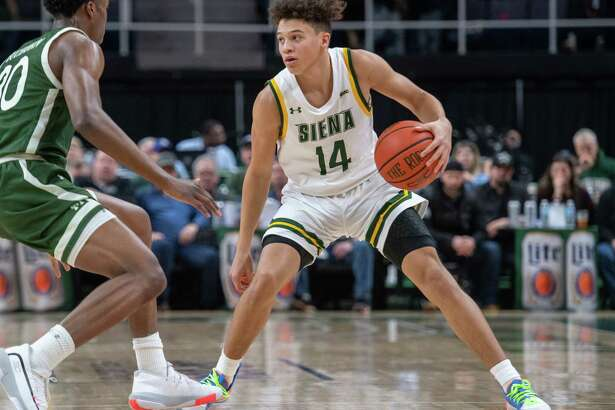 Siena College freshman Jordan King dribbles up court in front of Manhattan sophomore Elijah Buchanan during a Metro Atlantic Athletic Conference game at the Times Union Center in Albany, NY on Sunday, Feb. 16, 2020 (Jim Franco/Special to the Times Union.)
