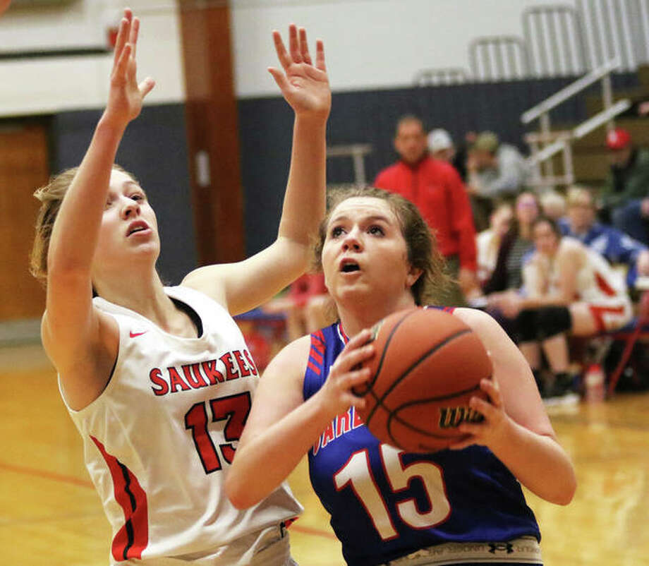 Carlinville's Gracie Reels (15) takes the ball to the basket on Pittsfield's Chloe Lemons on Thursday in the title game of the Carlinville Class 2A Regional. Photo: Greg Shashack / The Telegraph