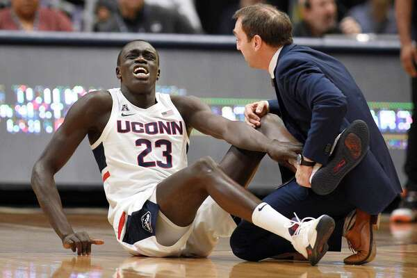 UConn's Akok Akok is tended to by head trainer James Doran in the first half of a game against Memphis on Feb. 16 in Hartford.