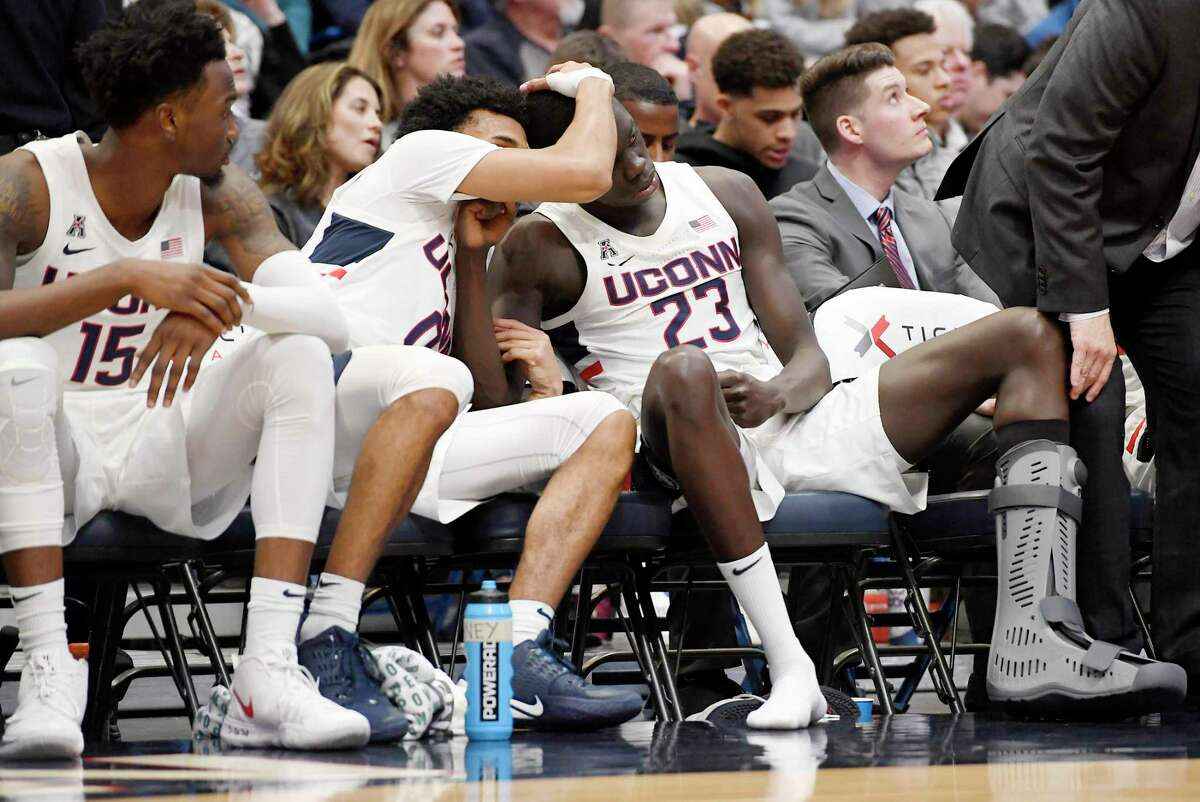 UConn's Akok Akok (23) is consoled by by teammate Jalen Gaffney, center, as Sidney Wilson, left, looks on, after Akok suffered an Achilles tendon injury on Sunday in Hartford.