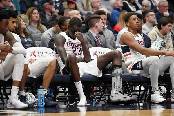 UConn's Akok Akok (23) reacts after returning to the bench with a boot on his left foot against Memphis on Sunday.