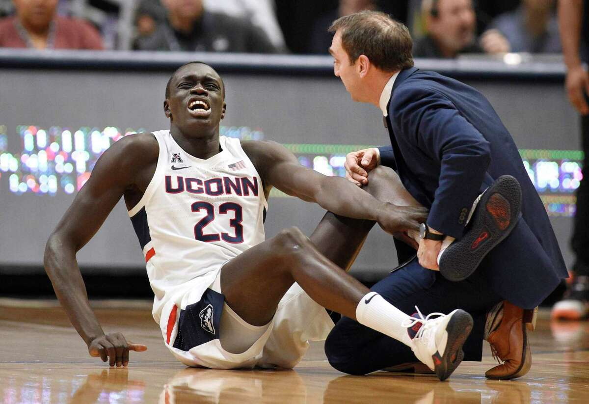 UConn's Akok Akok, left, reacts while being tended to by head trainer James Doran in the first half on Sunday.