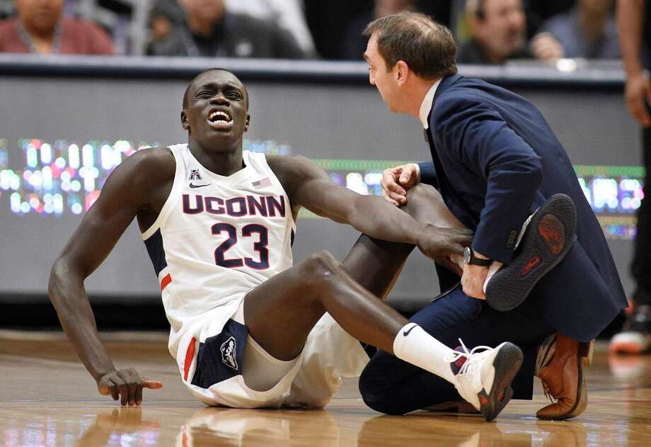 UConn's Akok Akok, left, reacts while being tended to by head trainer James Doran in the first half on Sunday. Photo: Jessica Hill / Associated Press / Copyright 2020 The Associated Press. All rights reserved.