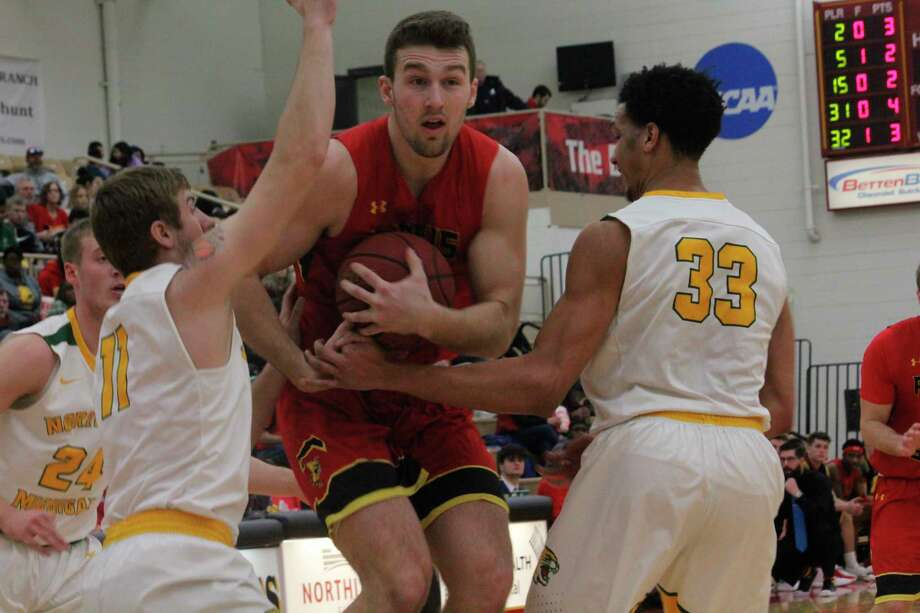 Ferris State's Mason Pline (with ball) tries to cut between Northern Michigan's Justin Kuehl (11) and Myles Howard (33) in Saturday's GLIAC game atWink Arena. (Pioneer photo/John Raffel)