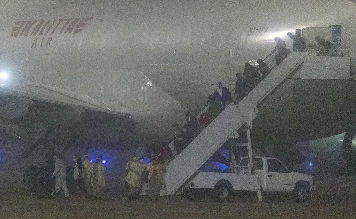 American passengers evacuated from a cruise ship in Japan disembark Monday morning, Feb. 17, 2020 from a Kalitta Air flight at Kelly Field. The passengers had been quarantined on the cruise ship as part of coronavirus control measures.