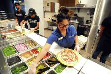 Pieology employees work the counter at the Stamford Town Center location, the pizzeria franchise's first location in Connecticut. A second Pieology will be located on Federal Road in Brookfield, Conn.