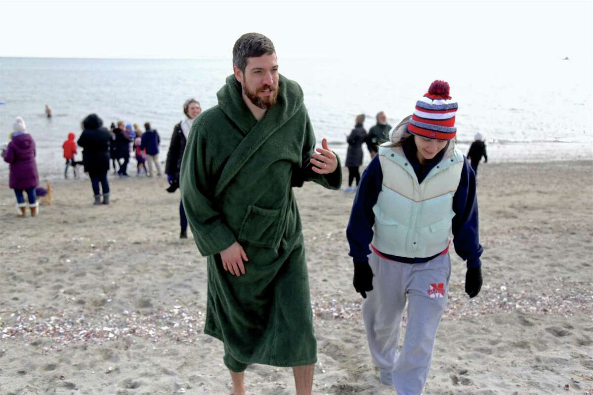 Amanda McAndrew of Monroe accompanies her husband Kevin back to shore after his plunge at the 2nd annual Polar Bear Plunge, organized by Save the Children, at Jennings Beach on Sunday, Feb. 16, 2020, in Fairfield, Conn.