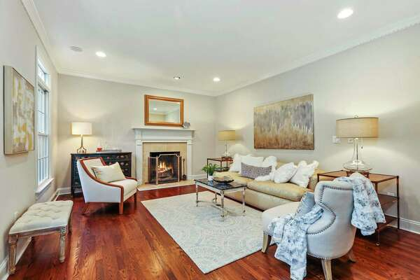 The formal living room has the first of the home's two fireplaces and dentil crown molding.