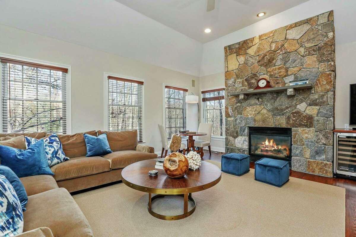 In the spacious den there is a tall vaulted ceiling, a stone fireplace, ceiling fan, and a dry bar area with a beverage refrigerator.