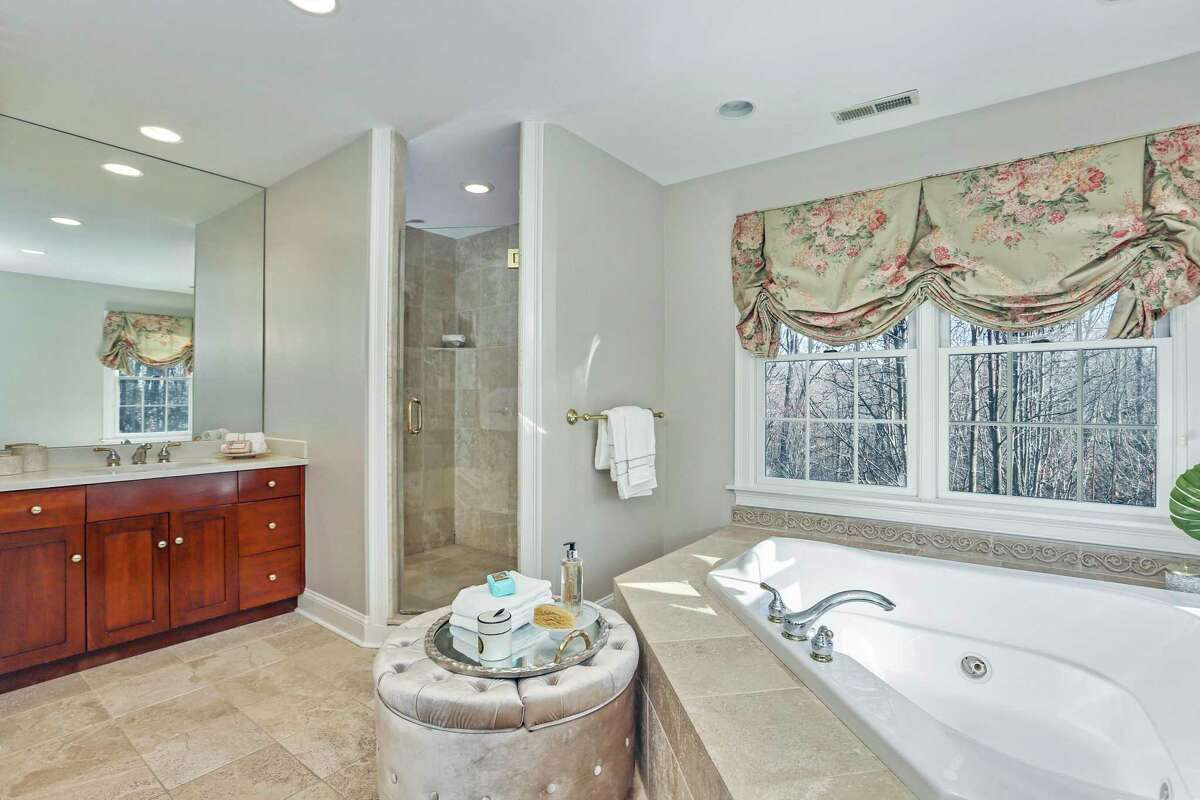 The luxurious master bath features a triangular jetted tub, shower, two separate vanities, and a water closet.