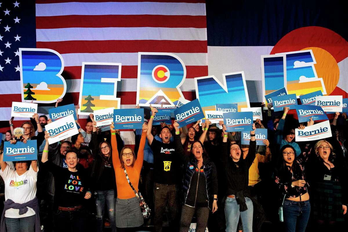 Supporters of Democratic presidential candidate Vermont Senator Bernie Sanders cheer during his campaign rally in Denver, Colorado on Feb. 16.