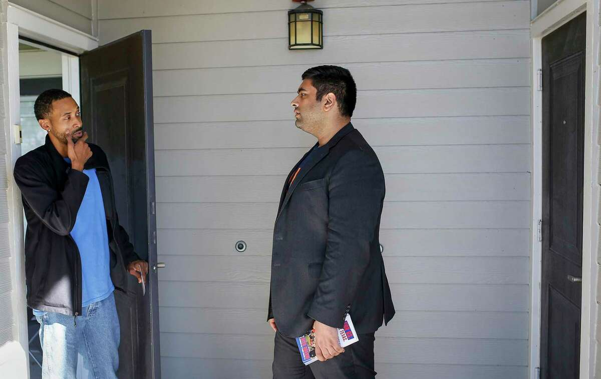"""Troy Lyles, left, talks to Rish Oberoi, a Democratic candidate for Texas House District 26, as Oberoi knocked on doors at the Marquis at Sugar Land apartments Thursday, Feb. 13, 2020, in Sugar Land. """"Gotta start the year off right,"""" Lyles said when asked why he planned to vote in a primary."""