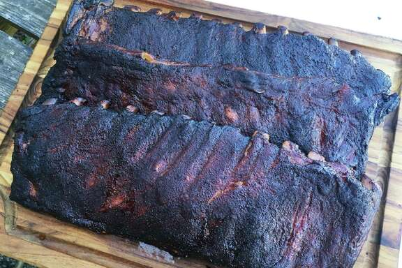 The finished pork ribs include, from top, the unwrapped, aluminum foil-wrapped, and butcher paper-wrapped slabs.