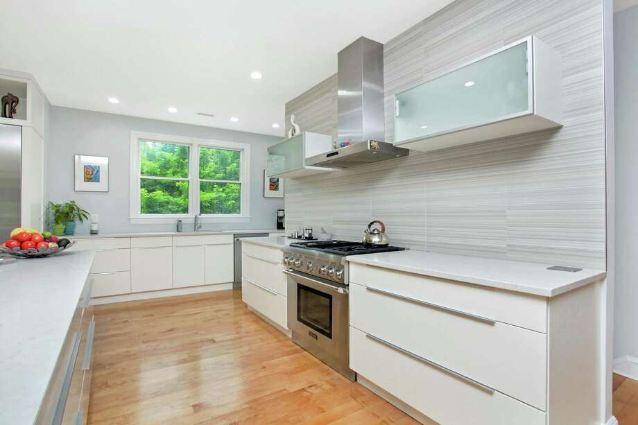 The large custom kitchen was designed by Fairfield-based Shore & Country Kitchens and features professional-grade Thermador appliances and a large walk-in pantry.