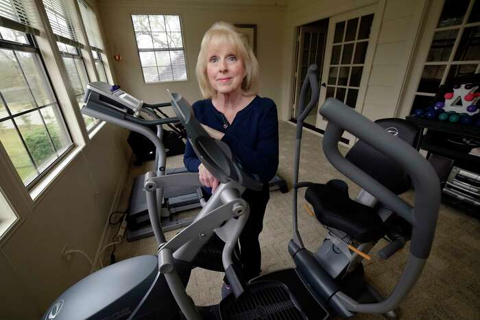 Bypass surgery patient Dessie Bice in her exercise room, with an elliptical machine, treadmill and rowing machine at her Woodlands home.