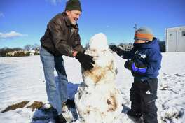Glenn Baum, of Buffalo, NY, builds a snowman with his grandson Oliver Baum, 5, of Milford, at Ray O'Connor Memorial Field in the Walnut Beach section of Milford, Conn. on Sunday, Jan. 19, 2020. It was one of the few times for measurable snow this winter. Based on readings at Sikorsky Memorial Airport in Stratford, this winter's current snow total of 10.1 inches is seven inches below the normal amount by mid-February