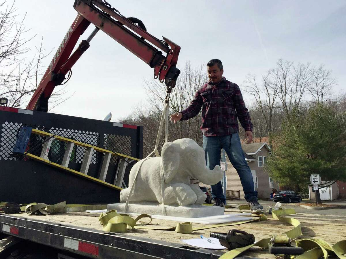 An 800 pound elephant statue gets a boost from Juan Carlos Olivares at Wilton Library.