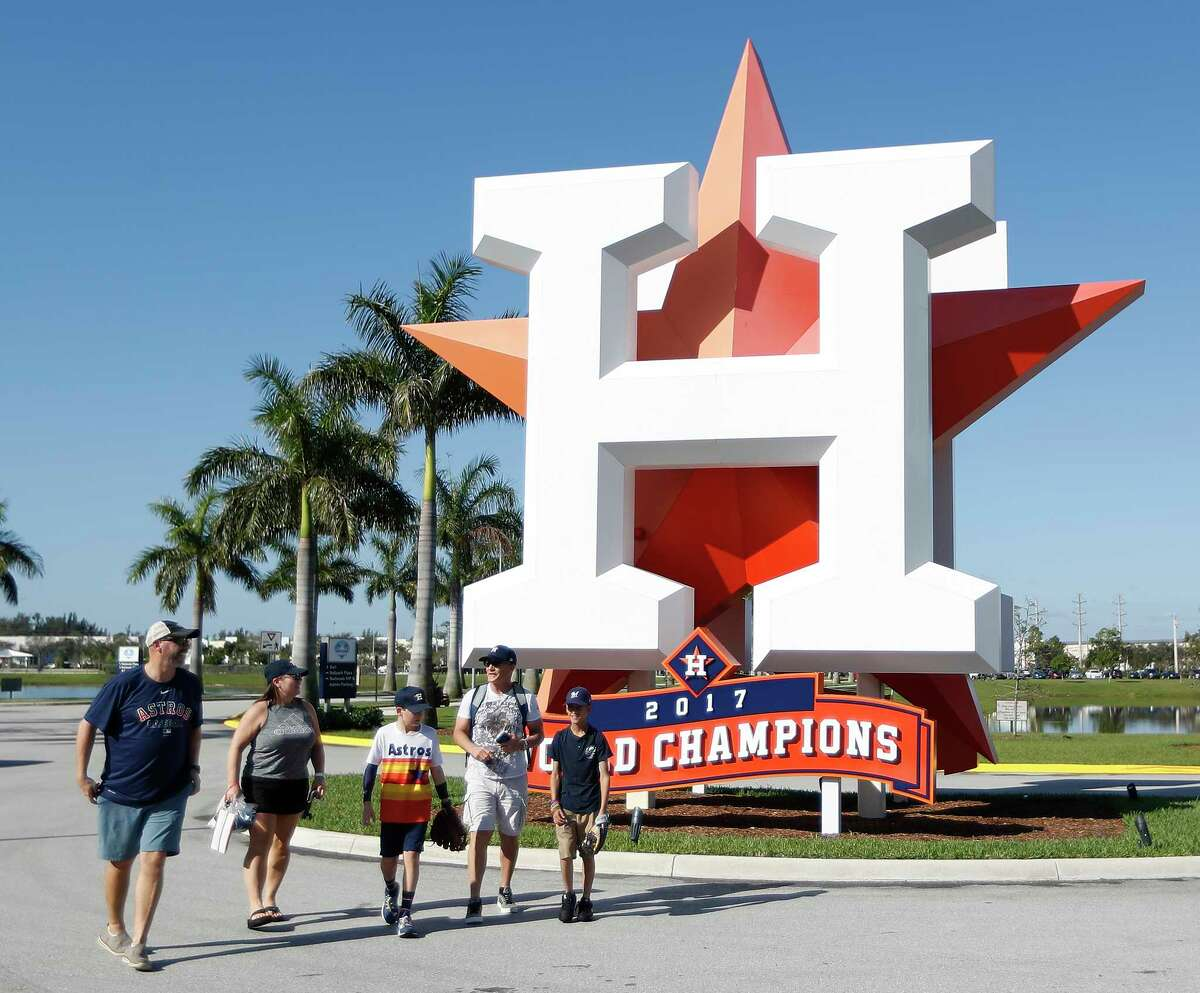 A family of Houston Astros fans walks past the giant H before the start of the first full-squad Houston Astros spring training workout at the Fitteam Ballpark of The Palm Beaches, in West Palm Beach , Monday, Feb. 17, 2020.