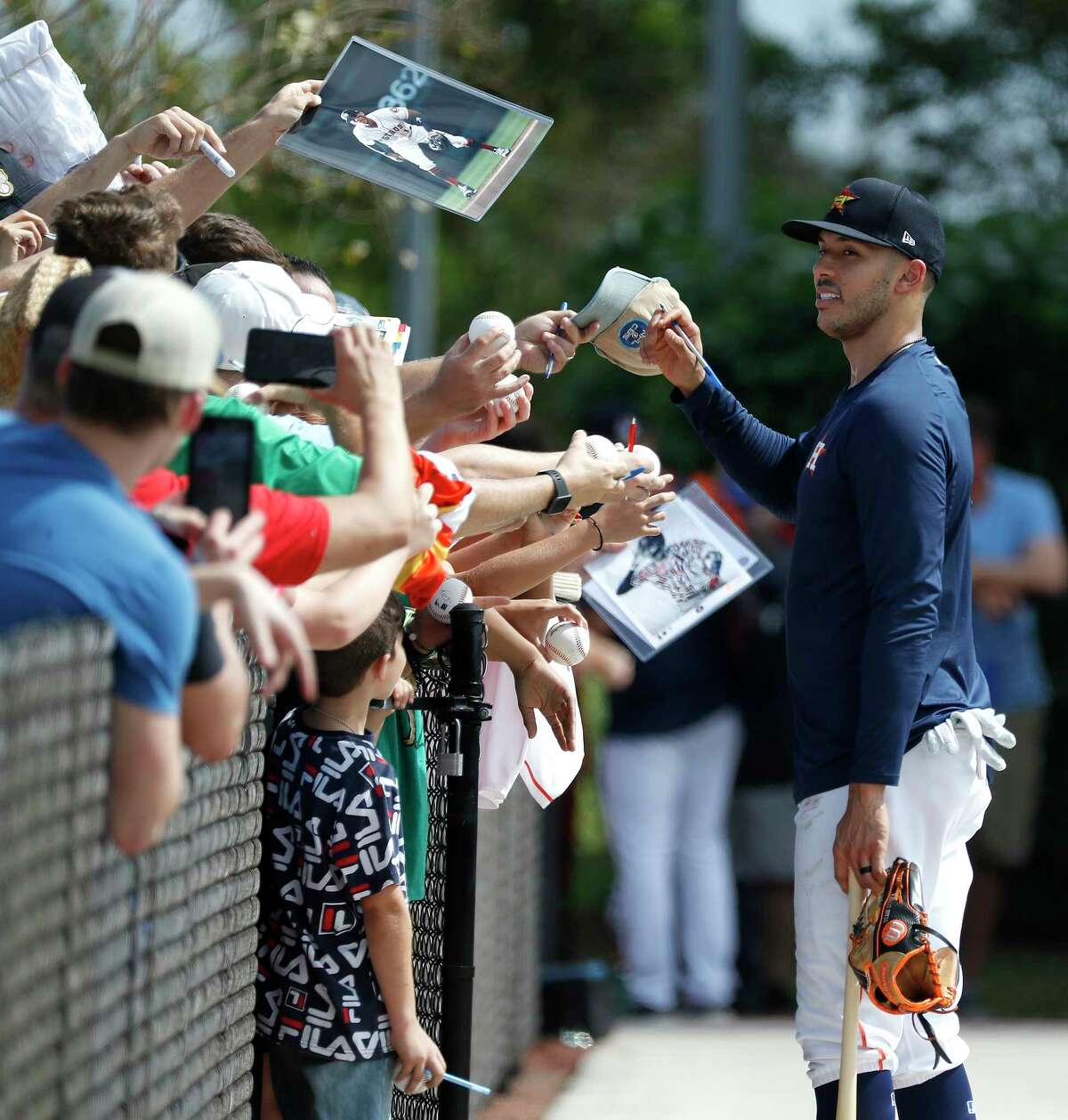 Houston Astros infielder Carlos Correa signs autographs for fans during the first full-squad Houston Astros spring training workout at the Fitteam Ballpark of The Palm Beaches, in West Palm Beach , Monday, Feb. 17, 2020.