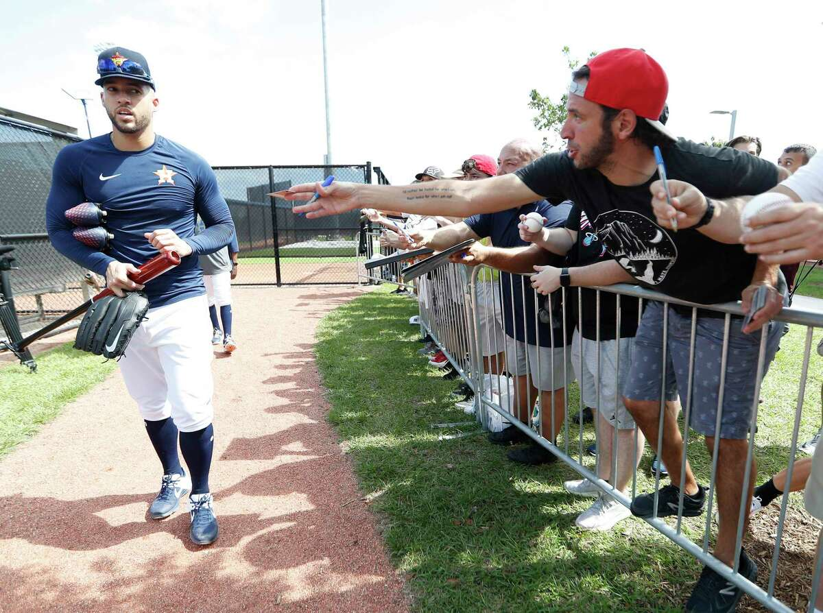 Fans ask Houston Astros outfielder George Springer (4) for his autograph during the first full-squad Houston Astros spring training workout at the Fitteam Ballpark of The Palm Beaches, in West Palm Beach , Monday, Feb. 17, 2020.
