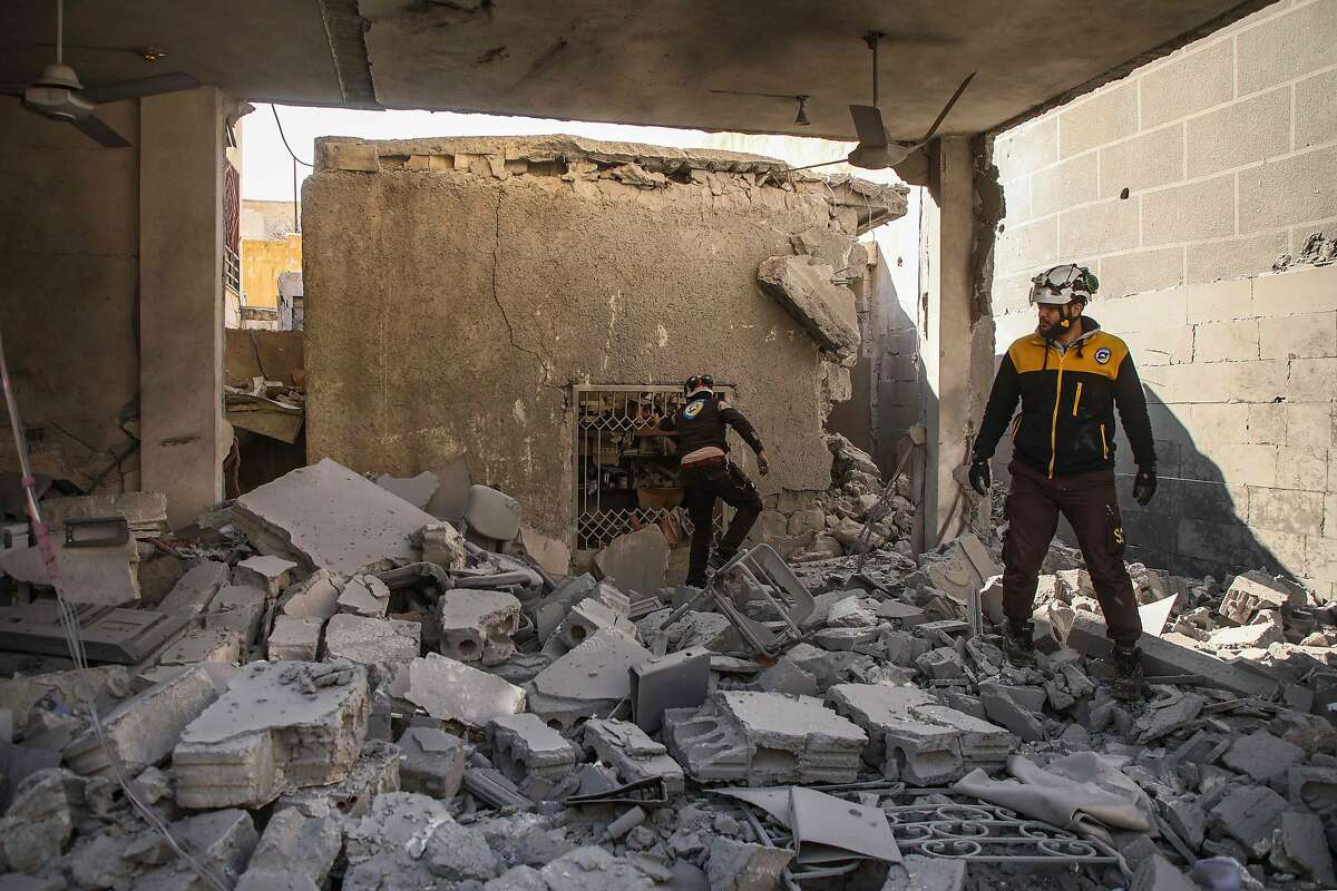 """Members of the Syrian Civil Defence, also known as the """"White Helmets"""", inspect through debris and rubble as they search for survivors at a destroyed hospital in the town of Darret Ezza, about 30 kilometres northwest of the northern Syrian city of Aleppo on February 17, 2020, after a reported air strike hit the building. (Photo by AAREF WATAD / AFP) (Photo by AAREF WATAD/AFP via Getty Images)"""