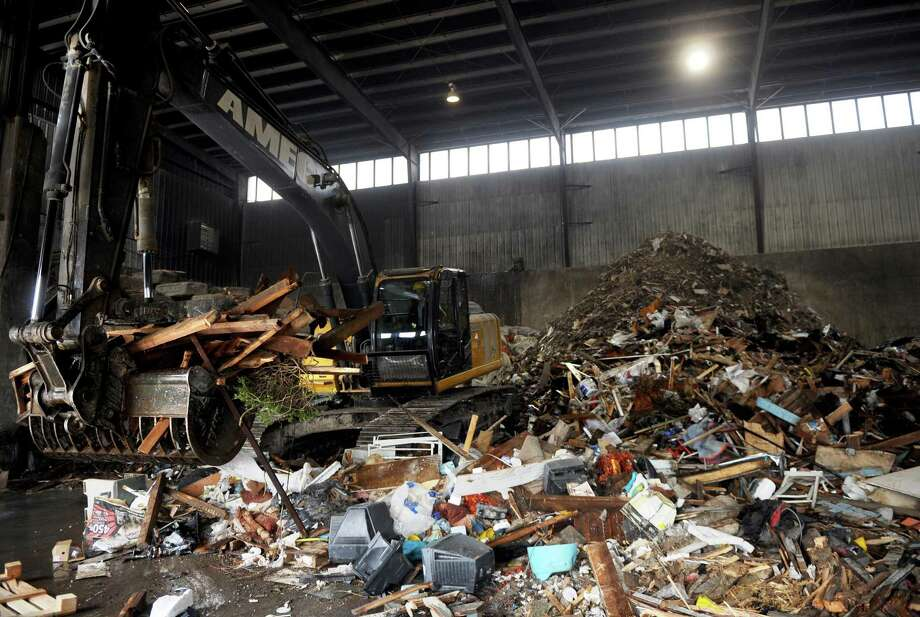 Employees move piles of materials to separate recyclables from trash to be sent to the landfill at AMEC Carting recycling plant in Norwalk. Photo: File Photo / Connecticut Post