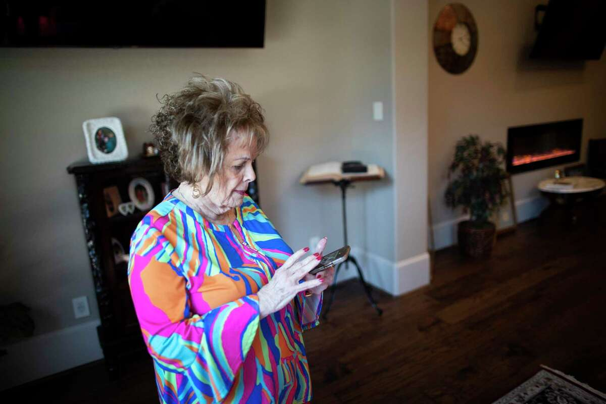 Pat Gandy, 81, uses her smartphone to open the window blinds at her home in River Plantation.