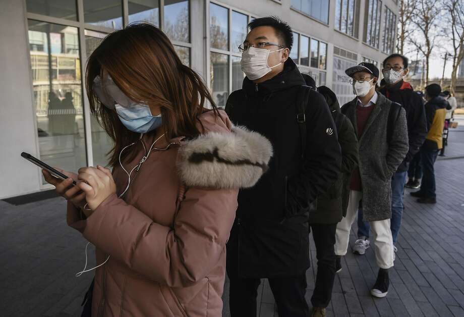 Chinese office workers wear protective masks as they line up to be checked and enter an office building Monday. Photo: Kevin Frayer / Getty Images