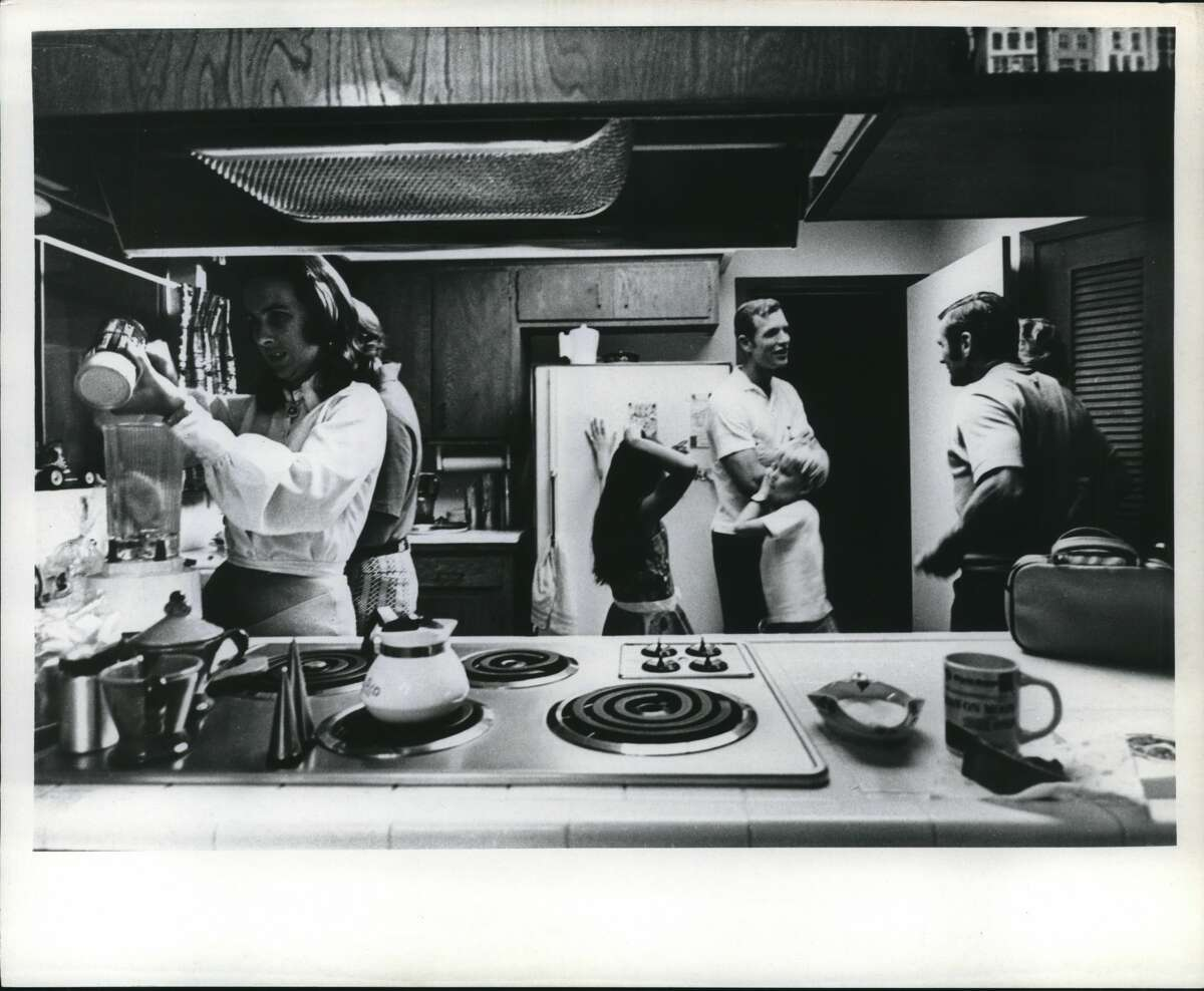Back from the Moon and in his own kitchen at home in Nassau Bay, Texas, Astronaut David R. Scott relaxes with his family. His wife, at left, prepares frozen orange juice for her family and guests. Colonel Scott, wearing casual clothes, a white shirt and slacks, stands next to the refrigerator with his two children, Tracey and Doug. He is chatting with friends of the family.