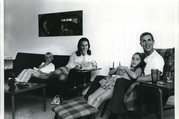 Back home again, Colonel David R. Scott and his family relax in their Nassau Bay, Texas, living room. Scott holds his daughter Tracey in a warm embrace, while his wife and son, Doug, sit close by on a couch. Mrs. Scott and Tracey get comfortable at home by removing their shoes.