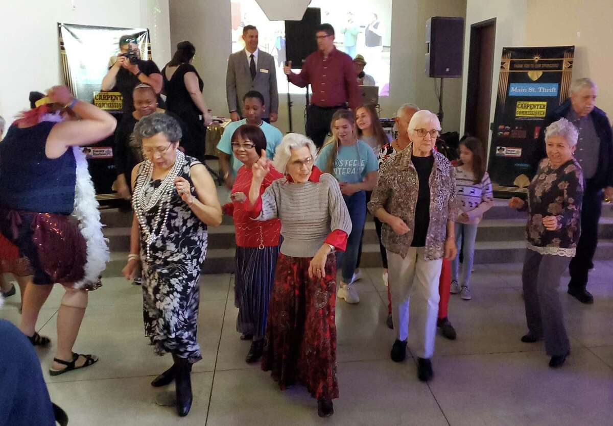 Martha Stahl, center, leads young and old alike in dancing to