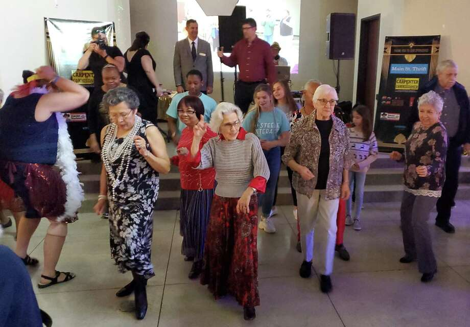 "Martha Stahl, center, leads young and old alike in dancing to ""Uptown Funk"" during Saturday's second annual Senior Soiree at the Noble Group Events Center in Cibolo. Photo: Jeff B. Flinn / Staff"