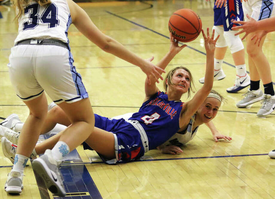 Carlinville's Jill Stayton (4) beats Breese Mater Dei's Shannon Lampe to a loose ball and passes to teammate in the first half Monday night in a semifinal at the Greenville Class 2A Sectional. Photo: Greg Shashack / The Telegraph
